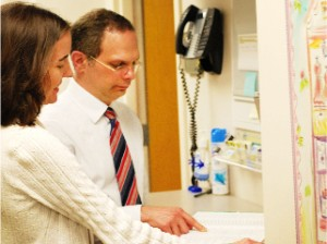 Surgeon pointing at patient file near phone in office